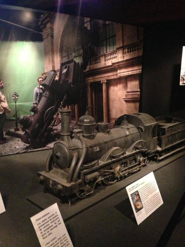 Behind the train is the actual footage of how they did the train crash in a movie.